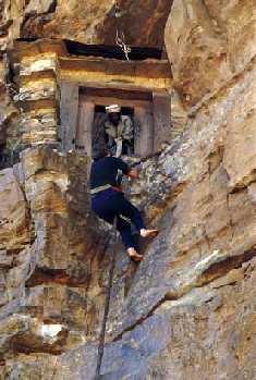 Picture of a man climbing up the cliff with the aid of a rope to reach the monastery of Saint Aregawi, Debre Damo
